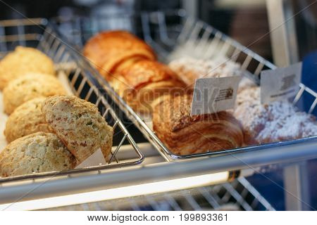 Coffee shop window with baked food pastries. Closeup macro group of round fresh cheese buns and turnovers in basket with white paper