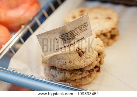 Coffee shop window with baked food pastries. Closeup macro stack pile of round fresh organic gluten free chocolate chips cookies in basket with white paper