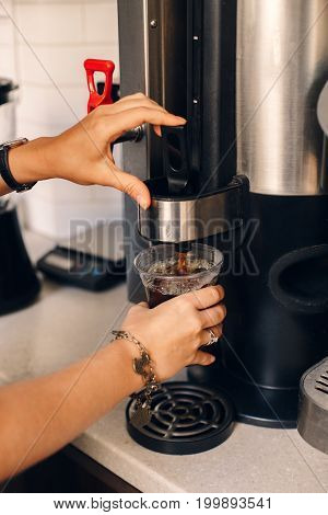 Closeup of Caucasian woman barista hands making pouring coffee from coffee machine in plastic transparent cup. Toned with film filters