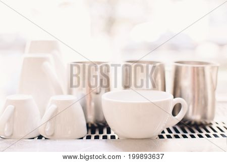 White coffee cups in coffee shop. Interior of cafe with tea mugs and milk jugs. Toned with filters with pastel colors. Retro vintage style.