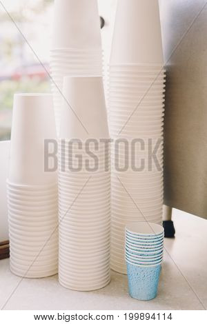 White coffee paper cups in coffee shop. Interior of cafe with tea mugs. Toned with filters. Retro vintage style.