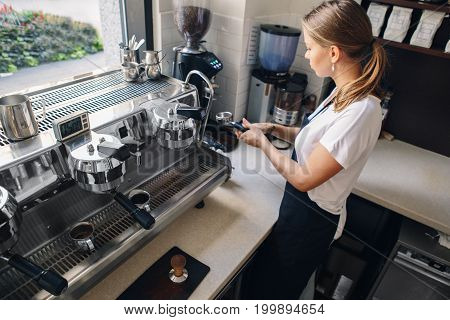 Portrait of Caucasian barista woman girl with filter holder grinding fresh roasted coffee beans. Preparing coffee in coffee shop cafe. View from top above overhead.