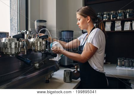 Portrait of young Caucasian woman barista wiping cleaning milk tip of professional espresso coffee machine. Small local business with hot drinks products. Busy life of local small business.