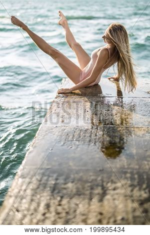 Cute ballerina sits on the concrete pier on the sea background. She leans on her hands while tilts her torso backward with outstretched legs. Girl wears a peach leotard. Sun shines on her. Vertical.