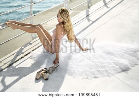 Young ballerina with closed eyes sits on the white tutu on the concrete seafront with metal fence. She wears a peach leotard and holds her legs on the fence. Next to her lying ballet shoes.