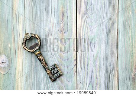 Ancient metal key on a wooden background close-up