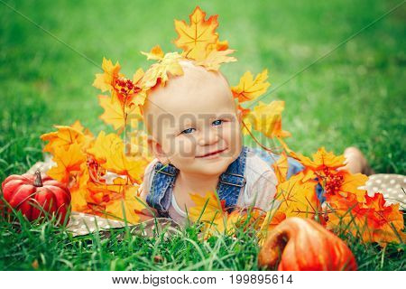 Portrait of cute funny adorable smiling Caucasian boy with blue eyes in t-shirt and jeans romper lying on grass field meadow. Baby in yellow autumn fall leaves pumpkins. Halloween Thanksgiving.