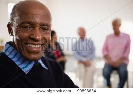 Close up Portrait of smiling senior man with friends in background at art class