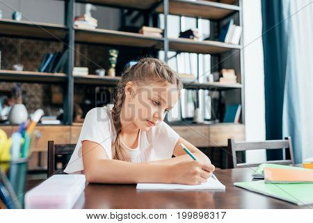 focused cute little girl writing in notebook and doing homework