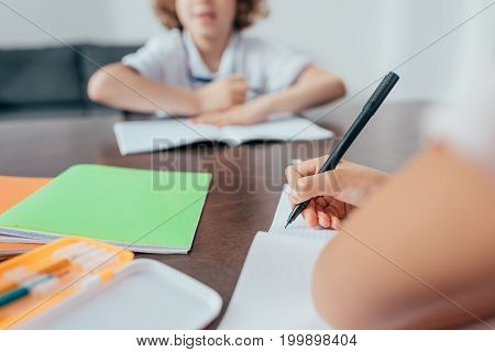 close-up shot of girl writing in notebook and boy blurred on background