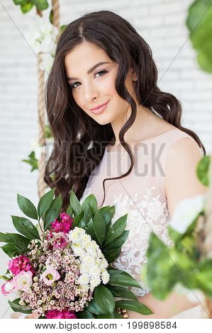 Beautiful Woman with Flowers Curly Hairstyle and Makeup. Brunette Model Girl
