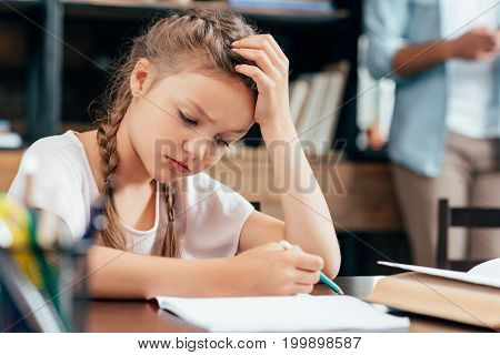 depressed little girl writing in notebook and doing homework