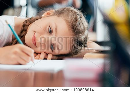 cute happy little girl writing in notebook and doing homework