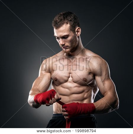 MMA Fighter Preparing Bandages For Training. Dark background.