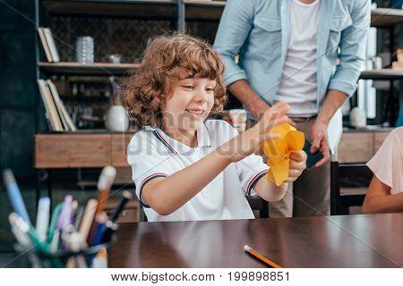 happy excited schoolboy crumpling color paper at home