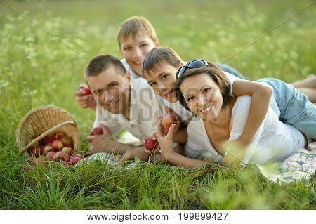 Family lying on grass near wicker basket full of apples