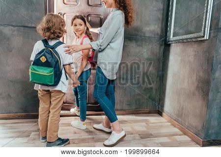 Young Mother Seeing Off Her Adorable Little Kids To School