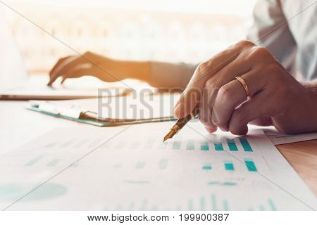 Businessman Holding Pen And Pointing Chart Report Paper On Desk And Using Laptop For Save Data.
