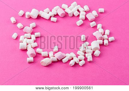 Colored twisted marshmallow on the pink background