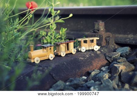 small wooden toy train on real railway tracks