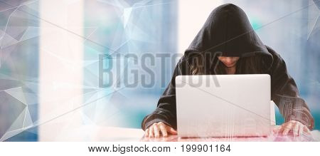 Female hacker sitting by laptop on table  against abstract glowing black background