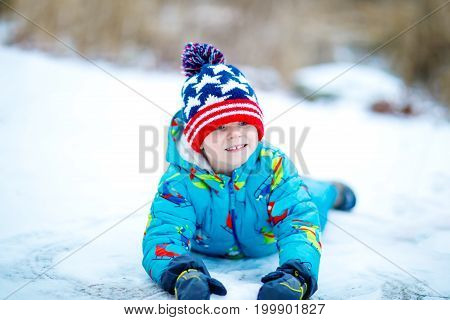 Funny little kid boy in colorful clothes playing outdoors during snowfall. Active leisure with children in winter on cold snowy days. Happy child on winter vacations in Lapland.