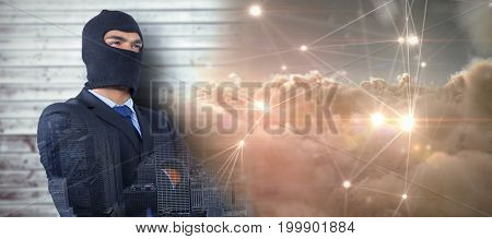 Male hacker standing with arms crossed against glowing dots with connecting lines over clouds