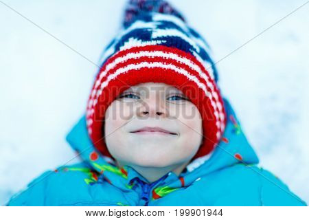 Funny little kid boy in colorful clothes playing outdoors during snowfall. Active leisure with children in winter on cold snowy days. Happy child on winter vacations in Sweden
