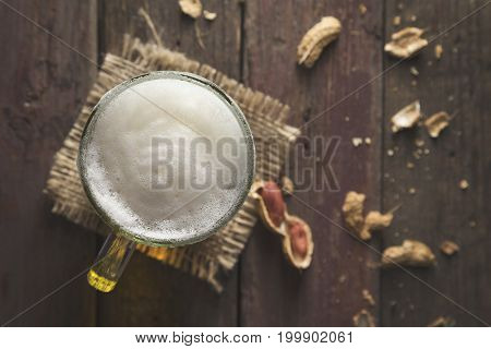 Top view of a mug of pale beer placed on a burlap cover with froth and some peanuts on a rustic wooden pub table. Focus on the froth