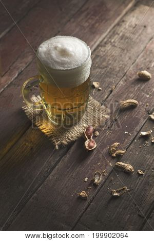 Mug of light beer with froth placed on a burlap cover and some peanuts on a rustic wooden pub table. Focus on the froth