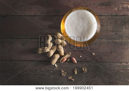 Top view of a glass of light beer with froth and some peanuts on a rustic wooden pub table. Focus on the peanuts