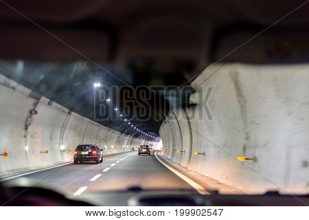 Night view from car back seat to tunnel on road to Rapallo, Italy