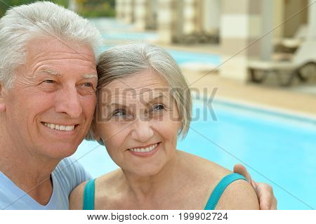 Senior couple relaxing at pool at hotel