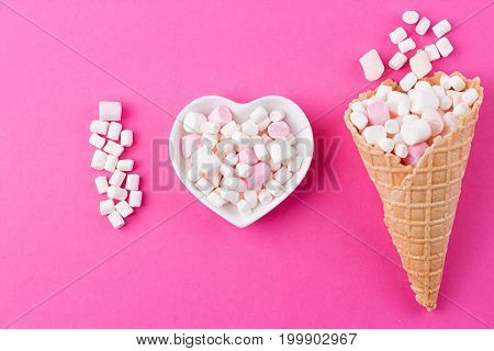 Love concept. Plate in the shape of heart with a marshmallow on a pink background. I love