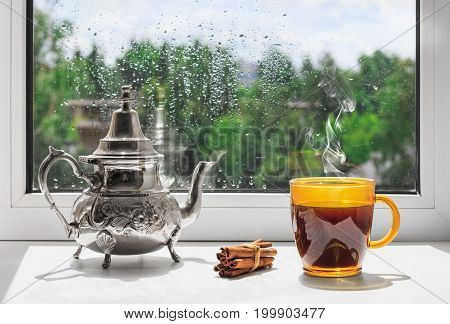 Cup of hot coffee on the windowsill. Outside the window the rain. Rainy weather behind the window.