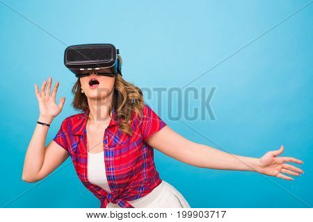 Technology, virtual reality, entertainment and people concept - happy young woman with virtual reality headset.