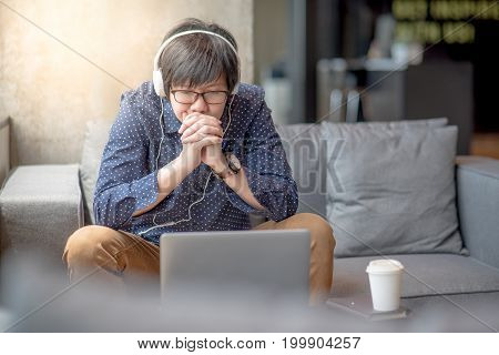 young asian man relaxing enjoy watching movie from his laptop computer with headphones on sofa urban lifestyle in living space