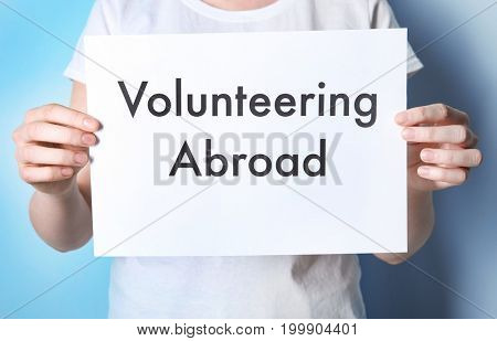 Woman holding sheet of paper with text VOLUNTEERING ABROAD on color background