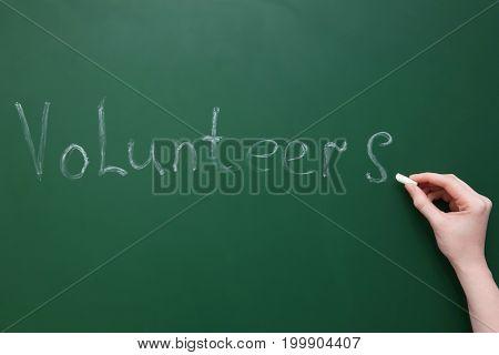 Woman writing word VOLUNTEERS on green chalkboard