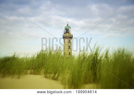 beautiful old lighthouse of Warnemuende with sand dunes and grass