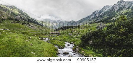 Panoramic view of the Fagaras mountains water stream and famous Transfagarasan road in Carpathians Romania spectacular wilderness scenery.