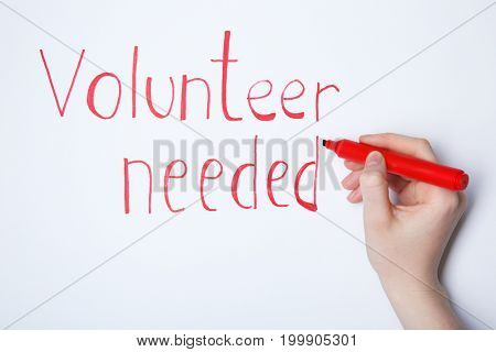 Woman writing text VOLUNTEER NEEDED on white background