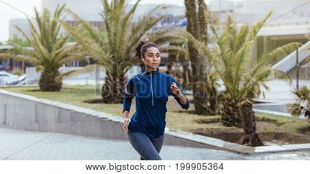 Woman runner in jogging outfit running on a street. Woman listening to music using earphones while running.
