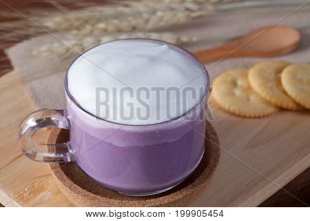 Close Up Hot Purple Milk With Biscuits On Wooden Plate On Wooden Table For Breakfast.