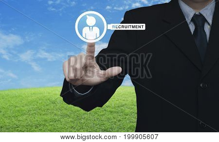 Businessman pressing businessman with magnifying glass icon over green grass field with blue sky Business recruitment concept