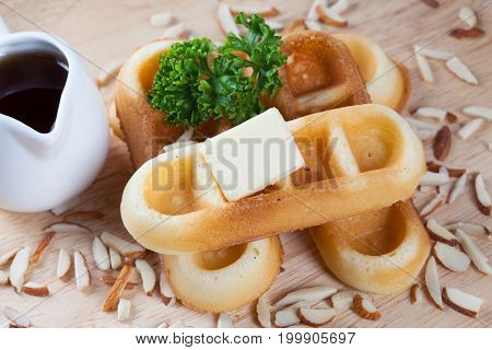 Close-up waffles and nut with parsley and cheese on top of waffles on wood plate for breakfast.