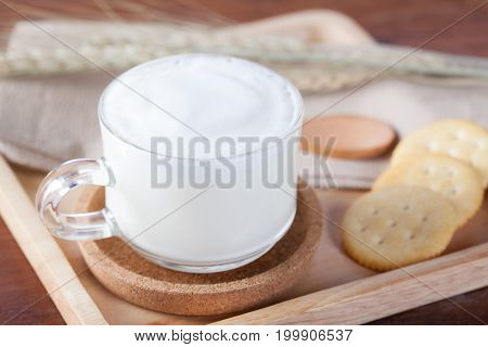 Hot Milk With Biscuits On Wooden Plate On Wooden Table For Breakfast.