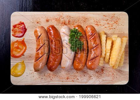 Grilled Sausage With Chili Powder And French Fries And Parsley On Top Of Sausage On Wooden Block On