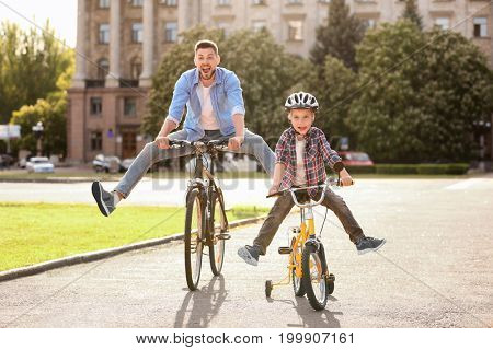 Dad and son riding bicycles outdoors