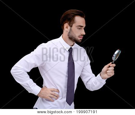 Handsome young man with magnifier on dark background